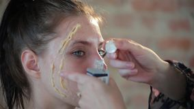 El artista de maquillaje profesional de la mujer del primer aplica la cera en cara de la muchacha linda joven para el maquillaje  almacen de video
