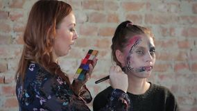 El artista de maquillaje profesional de la mujer del primer hace cera maquillaje plástico en forma de herida sangrienta para el c metrajes