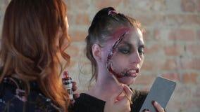 El artista de maquillaje profesional de la mujer del primer hace cera maquillaje plástico en forma de herida sangrienta para el c almacen de metraje de vídeo