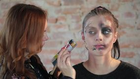 El artista de maquillaje profesional de la mujer del primer hace cera maquillaje plástico en forma de herida sangrienta para el c almacen de video