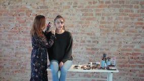 El artista de maquillaje profesional de la mujer hace cera maquillaje plástico en forma de herida sangrienta para el cine del art metrajes