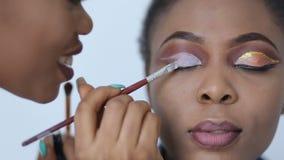 El artista de maquillaje profesional sonriente está aplicando los sombreadores de ojos en la cara del modelo africano joven atrac almacen de video