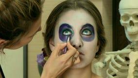 El artista de maquillaje que aplica la cara mexicana del cráneo del azúcar compone almacen de metraje de vídeo