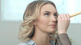 El artista de maquillaje que hace maquillaje de una muchacha rubia joven hermosa, aplica el polvo con el cepillo grande Imagen de archivo