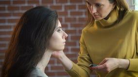 El artista de maquillaje que pone en maquillaje en el ` modelo s observa metrajes