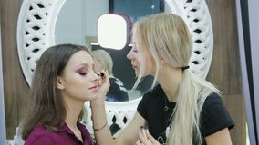 El artista de maquillaje realiza el colorante de la pestaña en un modelo hermoso en un salón de belleza almacen de metraje de vídeo