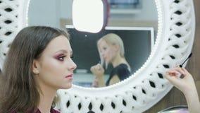 El artista de maquillaje realiza el colorante de la pestaña en un modelo hermoso en un salón de belleza almacen de video
