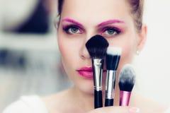 El artista de maquillaje sostiene cepillos del polvo Fotografía de archivo libre de regalías