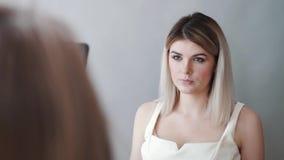 El artista de maquillaje toma las imágenes del modelo en el teléfono Labios oscuros, fondo gris maquillaje metrajes