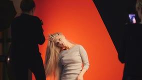 El artista de maquillaje toma una foto con smartphone en la moda entre bastidores durante la muchacha atractiva rubia que present Fotografía de archivo
