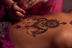 El artista de Mehendi pinta un ornamento de la alheña en un estómago hermoso del este de los girl's Imagenes de archivo
