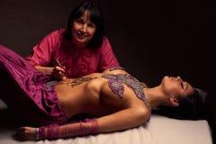 El artista de Mehendi pinta un ornamento de la alheña en un estómago hermoso del este de los girl's Fotografía de archivo