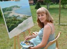 El artista de sexo femenino embarazada joven pinta una imagen, sentándose en un caballete imagenes de archivo