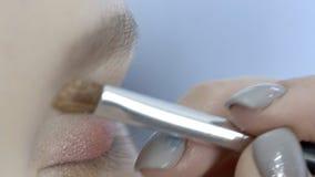 El artista de sexo femenino está haciendo maquillaje a la mujer en salón de belleza metrajes