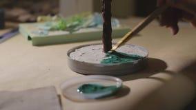 El artista de sexo femenino est? pintando el ?rbol hecho a mano del alambre antes de proceso del barniz metrajes