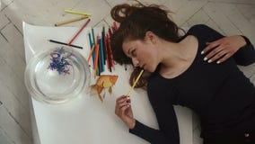 El artista de sexo femenino joven lindo hace una imagen de pequeños pescados de oro cercana para arriba en el fondo blanco Visión almacen de metraje de vídeo
