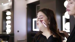 El artista de sexo femenino moreno del nake-up con la manicura roja hace tactos finales de sombreadores de ojos en los párpados d metrajes