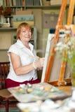 El artista de sexo femenino pinta una imagen en lona Imagenes de archivo