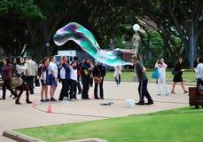El artista de sexo masculino de la calle hace burbujas de jabón grandes con dos palillos e hilos para el grupo de hembras en Hyde fotos de archivo