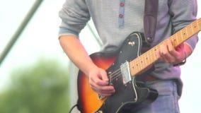 El artista de sexo masculino de la guitarra de la demostración del día juega el heavy, instrumento del hombre almacen de video