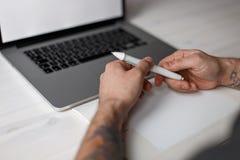 El artista de sexo masculino trabaja en un ordenador portátil y sostiene una pluma fotografía de archivo libre de regalías