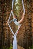 El artista de trapecio hermoso y agraciado realiza ejercicios en la seda aérea Fotos de archivo libres de regalías