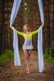 El artista de trapecio hermoso y agraciado realiza ejercicios en la seda aérea Fotografía de archivo libre de regalías