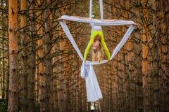 El artista de trapecio hermoso y agraciado realiza ejercicios en la seda aérea Imagen de archivo libre de regalías