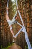 El artista de trapecio hermoso y agraciado realiza ejercicios en la seda aérea Imágenes de archivo libres de regalías