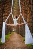 El artista de trapecio hermoso y agraciado realiza ejercicios en la seda aérea Foto de archivo libre de regalías