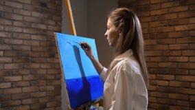 El artista del novato pinta el paisaje La muchacha del cuchillo de paleta hace un cielo azul hermoso 4K MES lento almacen de video