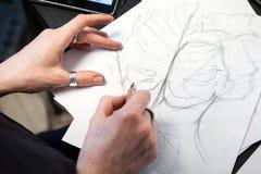 El artista del tatuaje de la muchacha dibuja un bosquejo Primer de manos Fotos de archivo