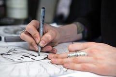 El artista del tatuaje de la muchacha dibuja un bosquejo Primer de manos Imágenes de archivo libres de regalías