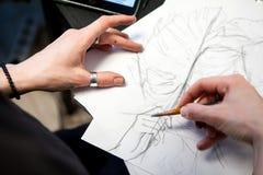 El artista del tatuaje de la muchacha dibuja un bosquejo Primer de manos Imagen de archivo libre de regalías