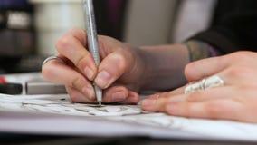 El artista del tatuaje de la muchacha dibuja un bosquejo Primer de manos almacen de metraje de vídeo