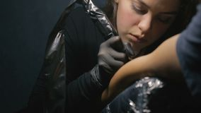El artista del tatuaje hace el tatuaje Dibujando un tatuaje en el cierre del hombro para arriba metrajes