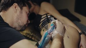 El artista del tatuaje hace el tatuaje en el estudio almacen de metraje de vídeo