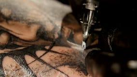 El artista del tatuaje hace el tatuaje en el estudio, tatuando en el cuerpo Cierre para arriba almacen de metraje de vídeo