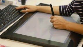 El artista dibuja en la tableta para dibujar El artista dibuja en la tableta para el primer de dibujo de manos metrajes