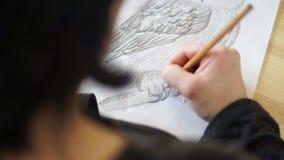 El artista dibuja la pata del búho