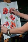 El artista dibuja una imagen en lona fotos de archivo