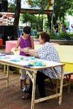 El artista enseñaba los niños al doblez el pape Imagen de archivo libre de regalías