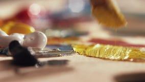 El artista está mezclando las pinturas de aceite amarillo y blanco con la brocha gruesa en la paleta metrajes