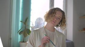 El artista feliz inspirado de sexo femenino con las mezclas del cepillo pinta en la paleta y las sonrisas muerden misterioso el l almacen de video