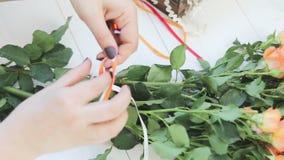 El artista floral de la mujer profesional, florista envuelve la cinta alrededor de ramo hermoso en el taller, floristería