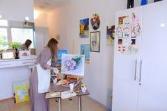 El artista Girl Holds Brush a disposición y dibuja en lona, coge el pH Fotografía de archivo libre de regalías
