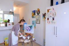 El artista Girl Holds Brush a disposición y dibuja en lona, coge el pH Imagen de archivo libre de regalías