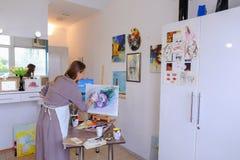 El artista Girl Holds Brush a disposición y dibuja en lona, coge el pH Fotos de archivo libres de regalías