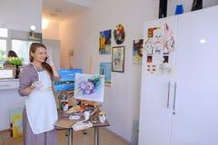 El artista Girl Holds Brush a disposición y dibuja en lona, coge el pH Imagen de archivo
