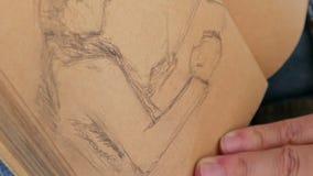 El artista gráfico dibuja el manual de las ilustraciones de la imagen del bosquejo almacen de video